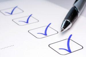 Stift mit blauen Häckchen auf Checkliste