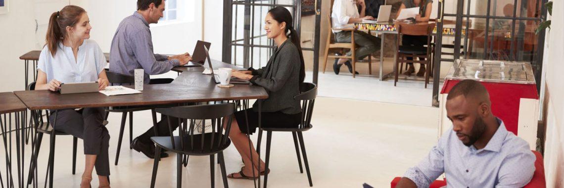 Office Manager sitzt auf Sofa in Großraumbüro